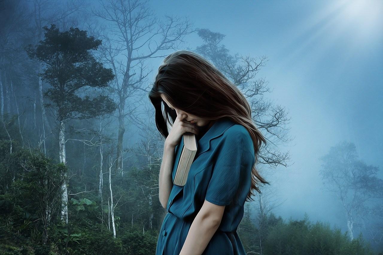 Depressive Frau in dunklem Wald